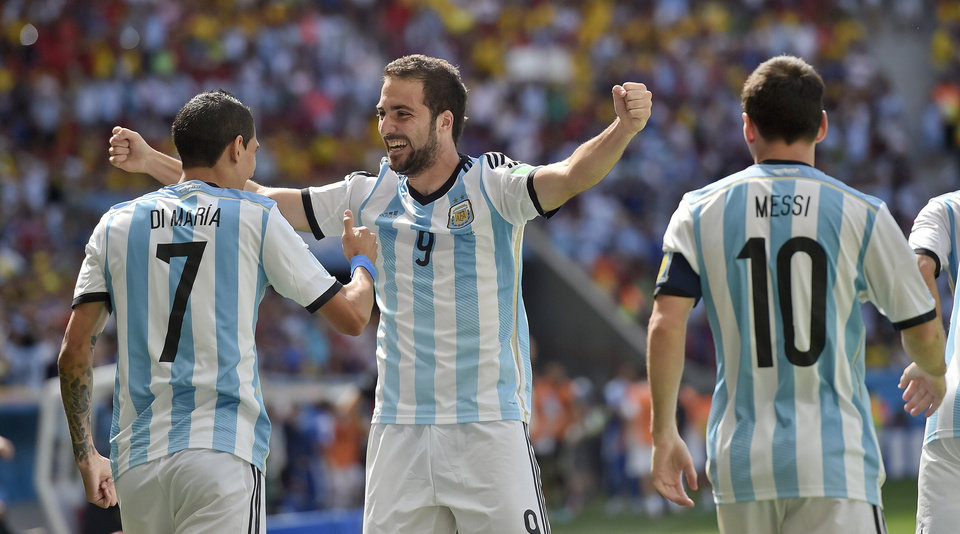 Photo - Argentina's Gonzalo Higuain, right, celebrates with Angel di Maria and Lionel Messi after he scored the opening goal during the World Cup quarterfinal soccer match between Argentina and Belgium at the Estadio Nacional in Brasilia, Brazil, Saturday, July 5, 2014. (AP Photo/Martin Meissner)