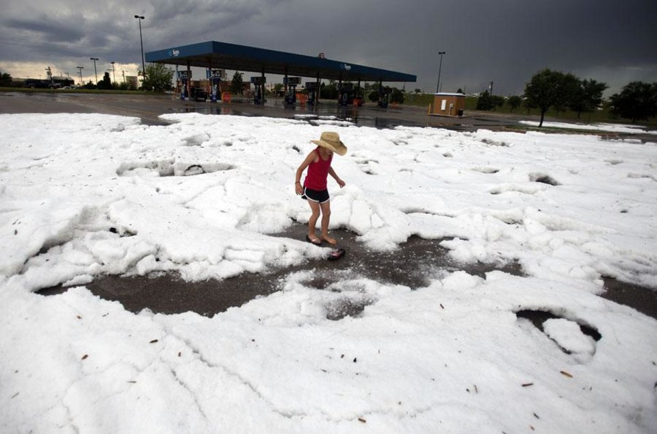 HAIL STORM: Riley Thompson, 8, of Edmond, Okla., plays on mound of hailstones in the Sam's Club parking lot on Pennsylvania Avenue near Memorial Road, Sunday, May 16, 2010 in Oklahoma City. Photo by Sarah Phipps, The Oklahoman  ORG XMIT: KOD