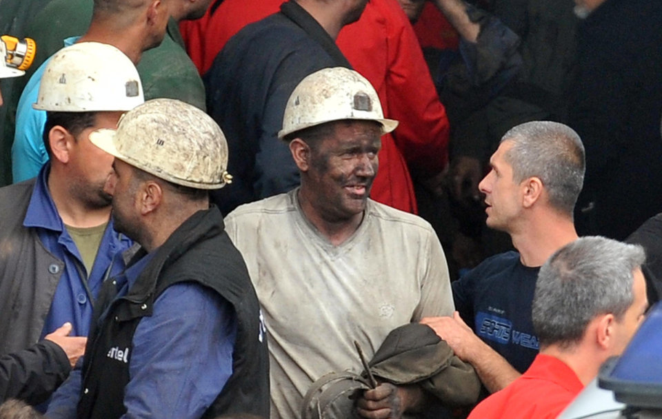 Photo - Coal miners carry out a fellow miner, center, who was injured while he was trapped in coal mine Raspotocje in Zenica,70 kms north of Sarajevo , Bosnia, on Friday, Sept.5, 2014 . Rescuers on Friday were pulling out some of the 34 miners who had been trapped deep inside a coal mine that collapsed in central Bosnia. Tired, their faces smeared with coal dust, the men came out of the Zenica mine one by one, after spending the night more than 500 meters (1,600 feet) below the ground. (AP Photo/Amel Emric)