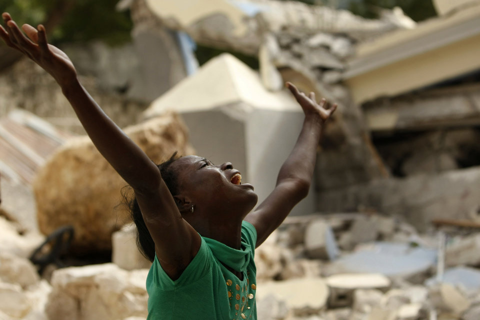 Photo - Cindy Terasme screams after seeing the feet of her dead 14-year-old brother Jean Gaelle Dersmorne in the rubble of the collapsed St. Gerard School in Port-au-Prince, Haiti, Thursday, Jan. 14, 2010.  A 7.0-magnitude earthquake hit Haiti Tuesday. (AP Photo/Gerald Herbert) ORG XMIT: HTIGH126