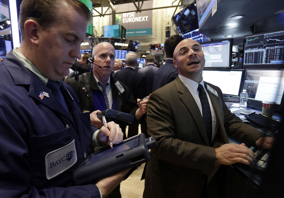 Photo - Specialist Henry Becker, right, works at his post on the floor of the New York Stock Exchange Friday, Dec. 21, 2012. Stocks opened sharply lower Friday on Wall Street after House Republicans called off a vote on tax rates and left federal budget talks in disarray 10 days before sweeping tax increases and government spending cuts take effect. (AP Photo/Richard Drew)