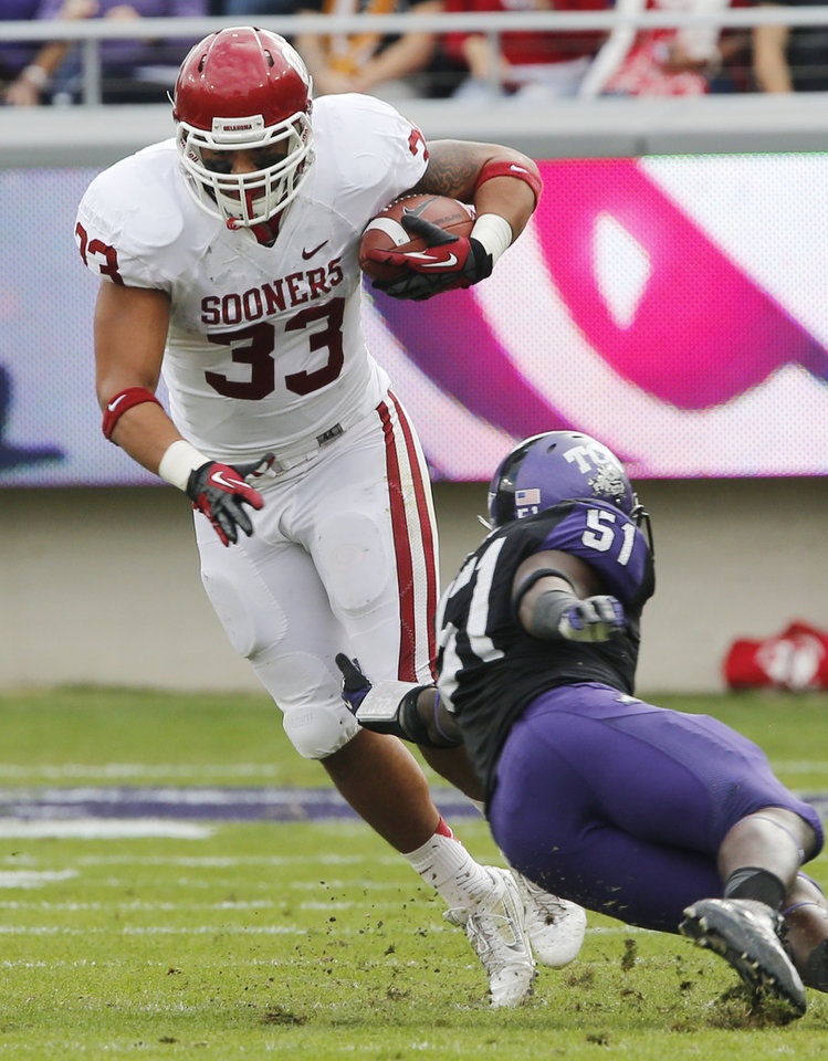 Photo - Oklahoma's Trey Millard (33) avoids a tackle attempt by TCU's Kenny Cain (51) during the college football game between the University of Oklahoma Sooners (OU) and the Texas Christian University Horned Frogs (TCU) at Amon G. Carter Stadium in Fort Worth, Texas, on Saturday, Dec. 1, 2012. Photo by Steve Sisney, The Oklahoman