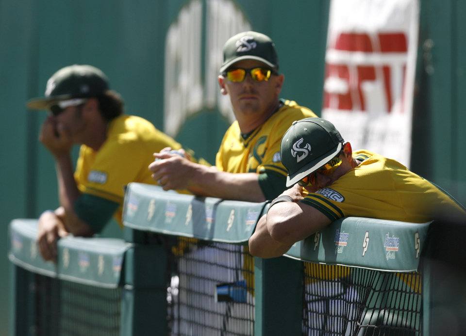 Photo - Sacramento State's Brandon Hunley, right, following a 6-5 loss to Cal Poly in an NCAA college baseball tournament regional game on Sunday, June 1, 2014, at Baggett Stadium at Cal Poly in San Luis Obispo, Calif. (AP Photo/Aaron Lambert)