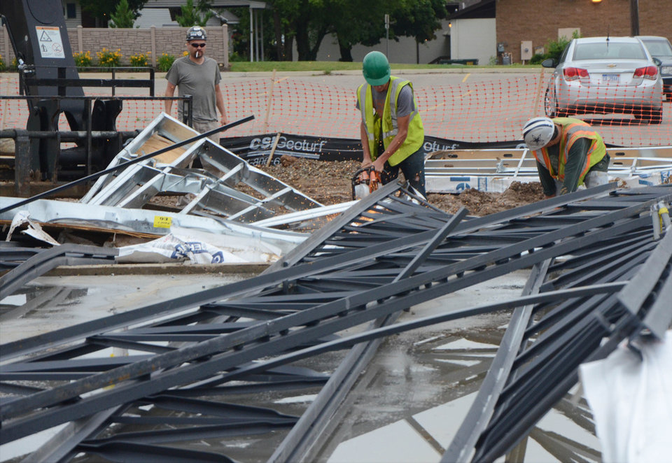 Photo - Workers remove storm debris at an urgent care construction site on Columbia Avenue in Battle Creek, Mich., Tuesday, July 1, 2014. Severe thunderstorms packing high winds knocked down trees and power lines across parts of Michigan, leaving more than 230,000 without power and injuring a firefighter. (AP Photo/Battle Creek Enquirer, John Grap)    NO SALES