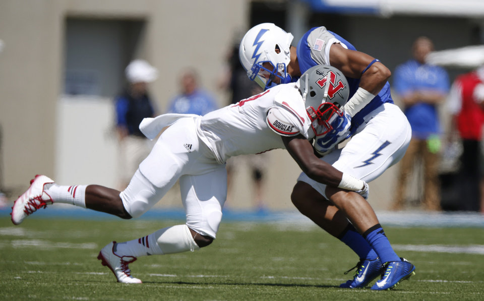 Photo - Nicholls State defensive back Christian Boutte, left, tackles Air Force wide receiver Jalen Robinette after he caught a pass in the first quarter of an NCAA college football game at Air Force Academy, Colo., on Saturday, Aug. 30, 2014. (AP Photo/David Zalubowski)