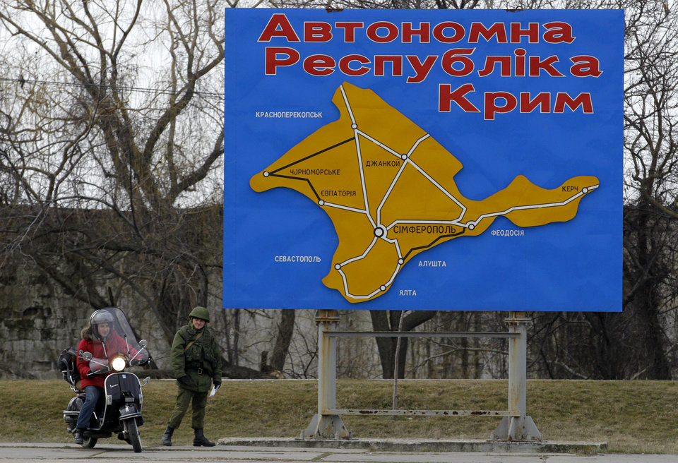 Photo - A pro-Russian soldier stands by a billboard with a map of Crimea and bearing the words