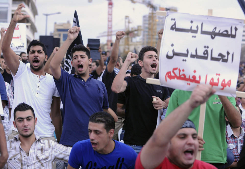 "Supporters of Sunni hardline preacher Sheikh Ahmad Assir hold a placard in Arabic that reads: ""for the hate-filled Zionist, die in your hatred,"" as they chant slogans during take part in a protest against an anti-Islam movie, in Beirut, Lebanon, Friday, Sept. 21, 2012. Anger over insults to Islam's Prophet Muhammad isn't enough to bring Lebanon's divided Sunni and Shiite Muslims together. The two sects, which have been locked in sometimes violent political competition, held separate protests Friday. Sunni protesters accused Shiite Hezbollah of using the demonstrators to distract from the fighting in neighboring Syria. AP photo"