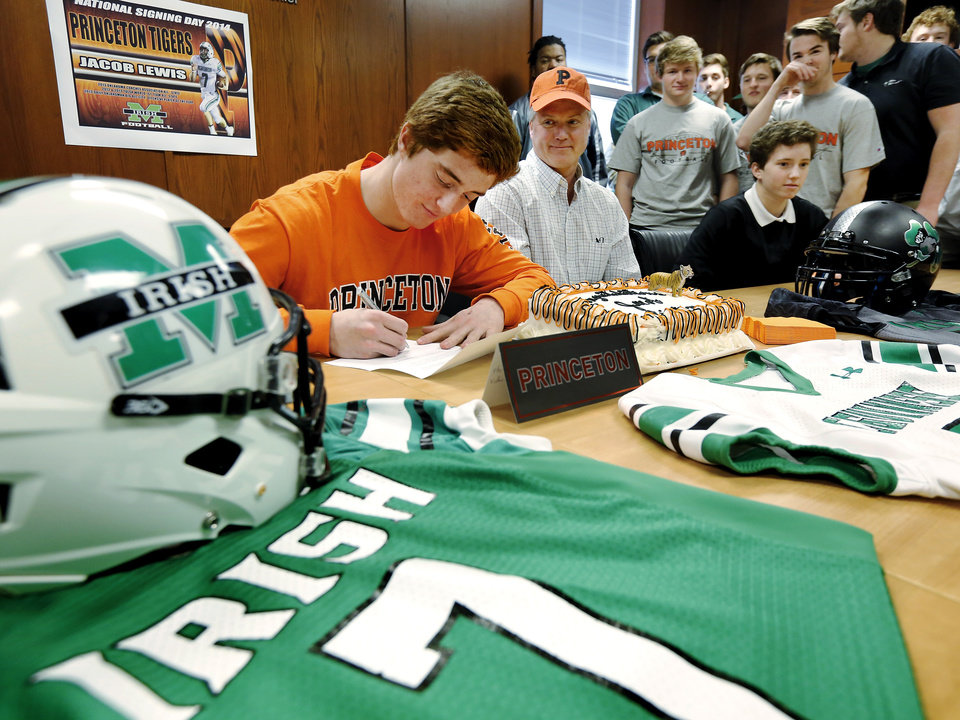 Photo - Jacob Lewis signs his letter as family and teammates watch. Seated beside Jacob is his dad, Jeff Lewis. Irish senior quarterback  Jacob Lewis signed a letter of intent to play at Princeton during a signing day ceremony at Bishop McGuinness High School on Wednesday, Feb. 5, 2014.    Photo by Jim Beckel, The Oklahoman