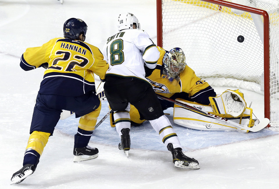 Dallas Stars right wing Reilly Smith (18) scores against Nashville Predators goalie Pekka Rinne (35), of Finland, in the second period of an NHL hockey game on Monday, Feb. 25, 2013, in Nashville, Tenn. Also defending against Smith is Scott Hannan (22). (AP Photo/Mark Humphrey)