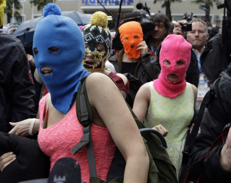 Photo - Russian punk group Pussy Riot members Nadezhda Tolokonnikova, in the blue balaclava, and Maria Alekhina, in the pink balaclava, make their way through a crowd after they were released from a police station, Tuesday, Feb. 18, 2014, in Adler, Russia. No charges were filed against Tolokonnikova and Alekhina along with the three others who were detained. (AP Photo/Morry Gash)