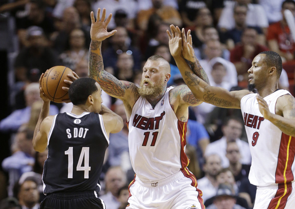 Photo - Brooklyn Nets guard Shaun Livingston (14) looks for an open teammate past Miami Heat forward Chris Andersen (11) and forward Rashard Lewis (9) during the first half of an NBA basketball game, Tuesday, April 8, 2014 in Miami. (AP Photo/Wilfredo Lee)