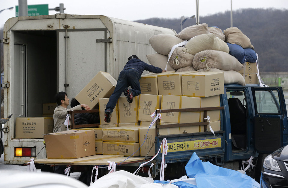 Photo - A South Korean man, center, unloads boxes transported from North Korea's Kaesong as reporters seek his comment upon arrival at the customs, immigration and quarantine office near the border village of Panmunjom, that has separated the two Koreas since the Korean War, in Paju, north of Seoul, South Korea, Tuesday, April 9, 2013. A few hundred South Korean managers, some wandering among quiet assembly lines, were all that remained Tuesday at the massive industrial park run by the rival Koreas after North Korea pulled its more than 50,000 workers from the complex. Others stuffed their cars full of goods before heading south across the Demilitarized Zone that divides the nations. (AP Photo/Lee Jin-man)