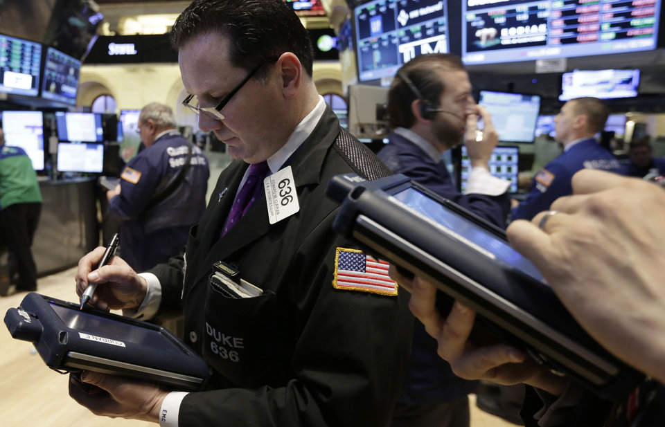 Photo - FILE - In this Feb. 28, 2014 file photo, trader Edward Curran, left, works on the floor of the New York Stock Exchange. Global stocks tumbled Monday, March 3, 2014, as tension over Russia's military advance into Ukraine and possible sanctions by Western governments intensified. (AP Photo/Richard Drew, File)