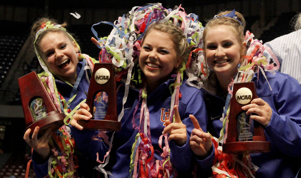 Photo - From left to right, Florida's Bridgey Caquatto, Morgan Frazier and Claire Boyce celebrate after being crowned co-champions with Oklahoma during the NCAA college women's gymnastics championships on Saturday, April 19, 2014, in Birmingham, Ala. (AP Photo/Butch Dill)