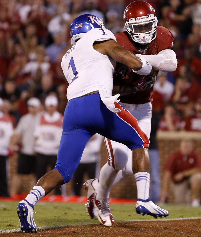 Photo - OU's Damien Williams (26) scores a touchdown past KU's Lubbock Smith (1) during the college football game between the University of Oklahoma Sooners (OU) and the Kansas Jayhawks (KU) at Gaylord Family-Oklahoma Memorial Stadium in Norman, Okla., Saturday, Oct. 20, 2012. Photo by Bryan Terry, The Oklahoman