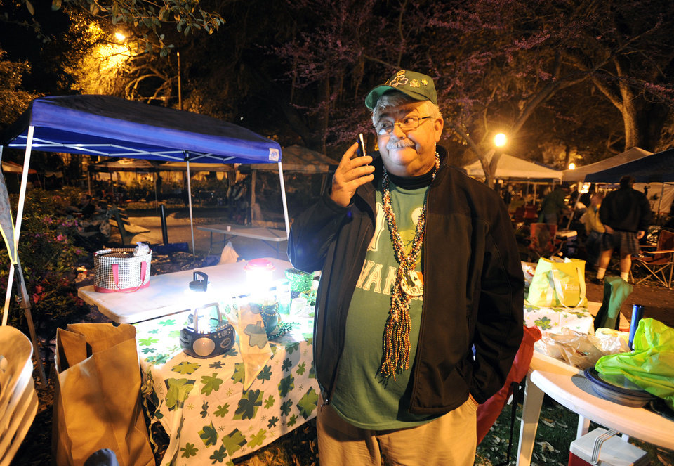 Photo - Kevin Rippman, of Savannah, Ga., checks in with his wife on the phone after setting up before dawn in Lafayette Square before Savannah's 189-year-old St. Patrick's Day parade, Saturday, March 16, 2013, in Savannah, Ga. St. Patrick's Day falls on March 17, which is Sunday. But a number of cities, including Savannah, New York and Chicago are all holding parades Saturday to take advantage of the full weekend. (AP Photo/Stephen Morton)