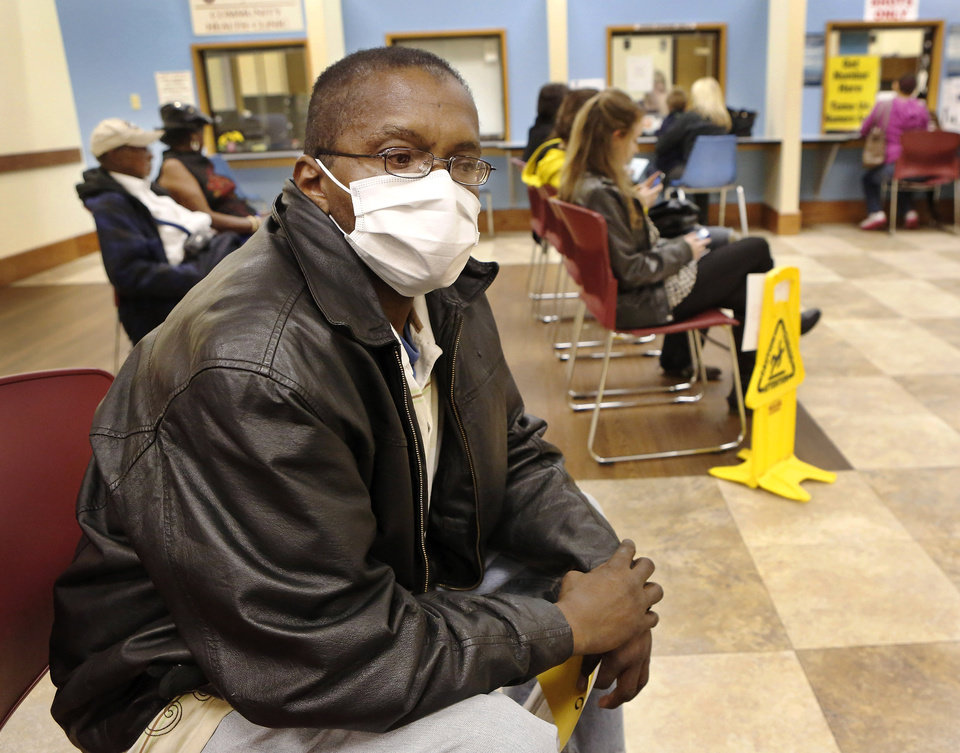 Photo - Walter Harris, Oklahoma City, wears a protective mask while sitting with several dozen other clients in the waiting room at the Oklahoma City/County Health Department Thursday afternoon, Jan. 10, 2013.  Harris came for a flu shot and said he wore the mask to reduce the risk of catching germs while he was in the waiting area.  Photo by Jim Beckel, The Oklahoman