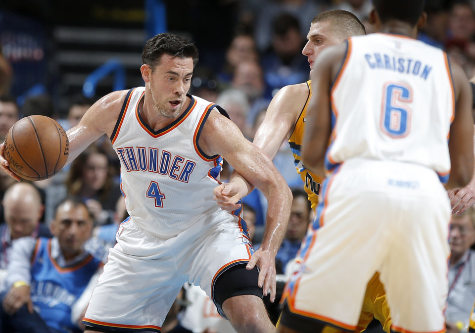 Photo - Oklahoma City's Nick Collison (4) goes past Denver's Nikola Jokic (15) during an NBA basketball game between the Oklahoma City Thunder and the Denver Nuggets at Chesapeake Energy Arena in Oklahoma City, Wednesday, April 12, 2017. Photo by Bryan Terry, The Oklahoman