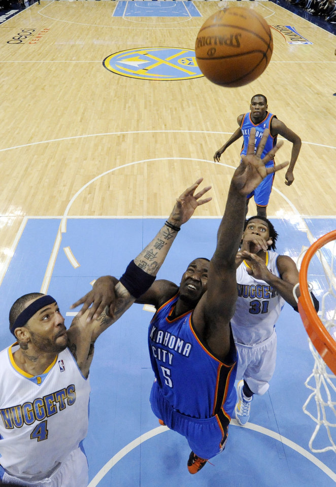 Oklahoma City Thunder center Kendrick Perkins (5) goes up for a shot against Denver Nuggets forward Kenyon Martin (4) and Nene (31) during the second half of game 3 of a first-round NBA basketball playoff series Saturday, April 23, 2011, in Denver. Oklahoma City beat Denver 97-94 to take a 3-0 series lead. (AP Photo/Jack Dempsey)