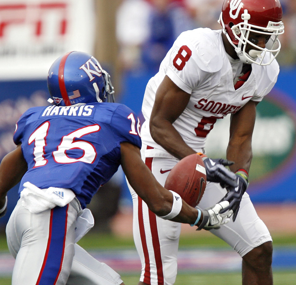 Photo - Oklahoma's Brandon Caleb (8) drops a pass againt the defense of Kansas' Chris Harris (16) during the first half of the college football game between the University of Oklahoma Sooners (OU) and the University of Kansas Jayhawks (KU) on Saturday, Oct. 24, 2009, in Lawrence, Kan. Photo by Chris Landsberger, The Oklahoman