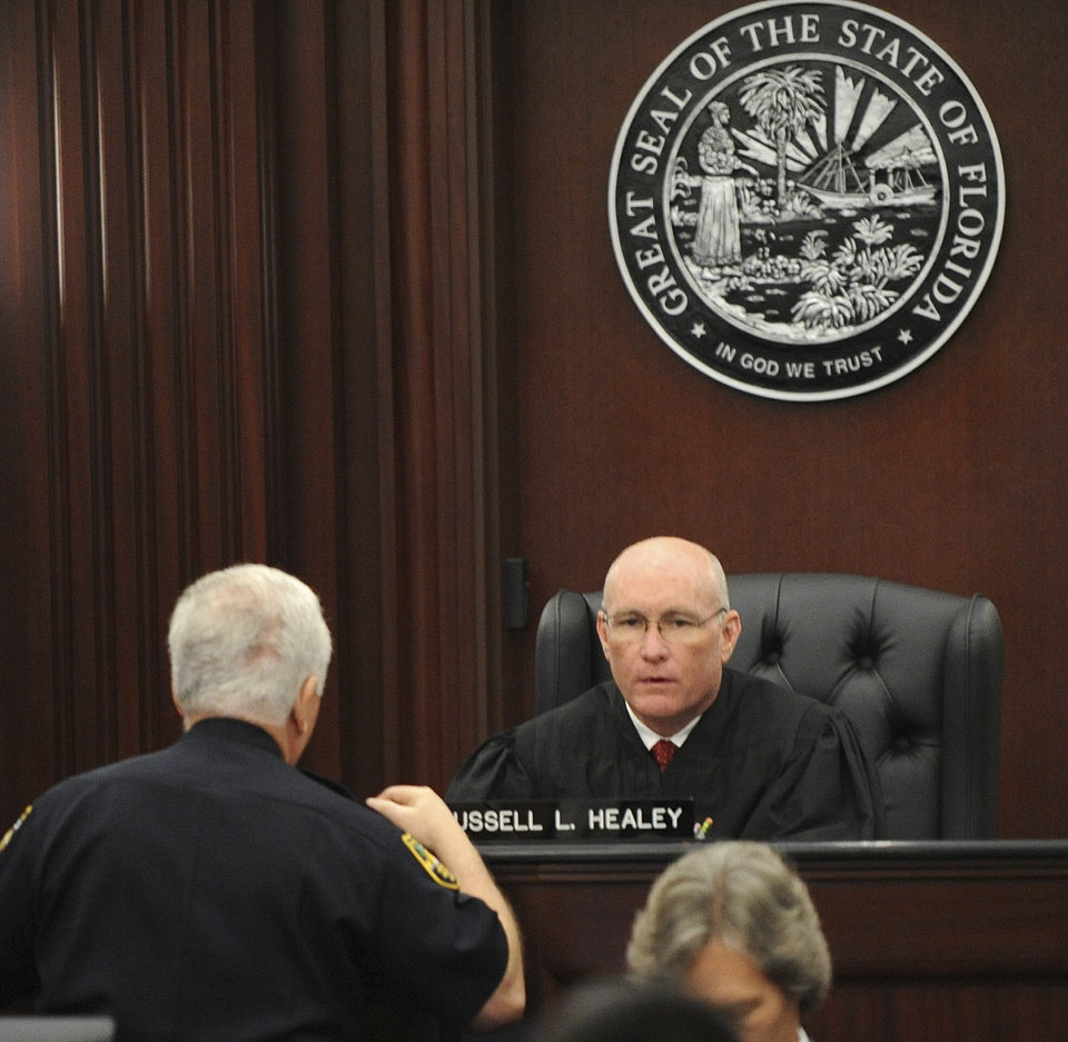 Photo - Judge Russell Healey talks with Supervisor of Courthouse Baliffs, Major Steven Weintraub, about the jury asking to have the large evidence boxes moved out of the jury room into an evidence locker to give them more room as the jury deliberates after the trial of Michael Dunn, Saturday, Feb. 15, 2014 in Jacksonville, Fla. Dunn is charged with fatally shooting 17-year-old Jordan Davis after an argument over loud music outside a Jacksonville convenient store in 2012. (AP Photo/The Florida Times-Union, Bob Mack, Pool)