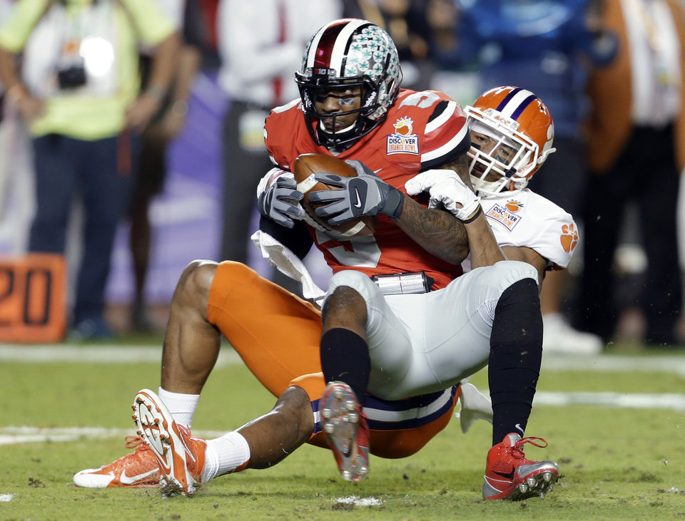 Photo - Ohio State quarterback Braxton Miller is brought down by Clemson defensive end Vic Beasley during the first half of the Orange Bowl NCAA college football game, Friday, Jan. 3, 2014, in Miami Gardens, Fla. (AP Photo/Lynne Sladky)
