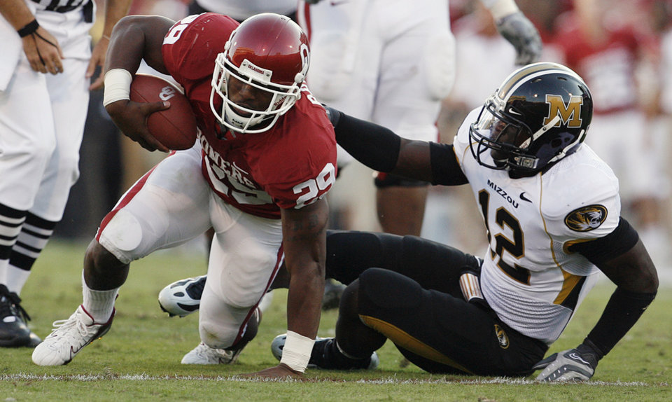 Photo - Oklahoma's Chris Brown (29) get up after a hit by Missouri's Sean Weatherspoon (12) to race for a touchdown that was called back after a replay review during the first half of the college football game between the University of Oklahoma Sooners (OU) and the University of Missouri Tigers (MU) at the Gaylord Family Oklahoma Memorial Stadium on Saturday, Oct. 13, 2007, in Norman, Okla.By STEVE SISNEY, The Oklahoman