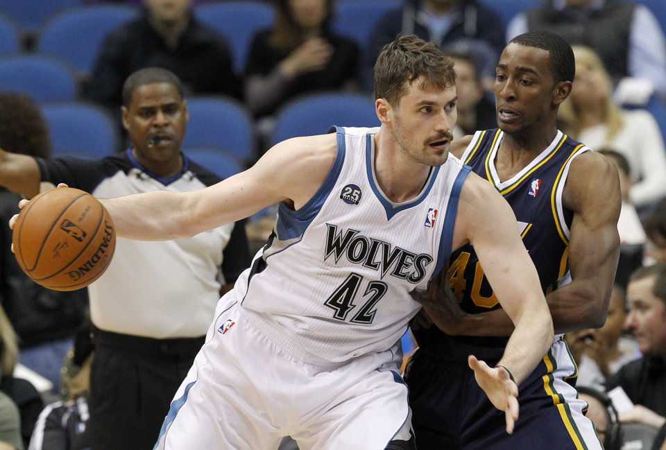 Photo - Minnesota Timberwolves forward Kevin Love (42) drives against Utah Jazz forward Jeremy Evans, right, during the first quarter of an NBA basketball game in Minneapolis, Wednesday, April 16, 2014. (AP Photo/Ann Heisenfelt)