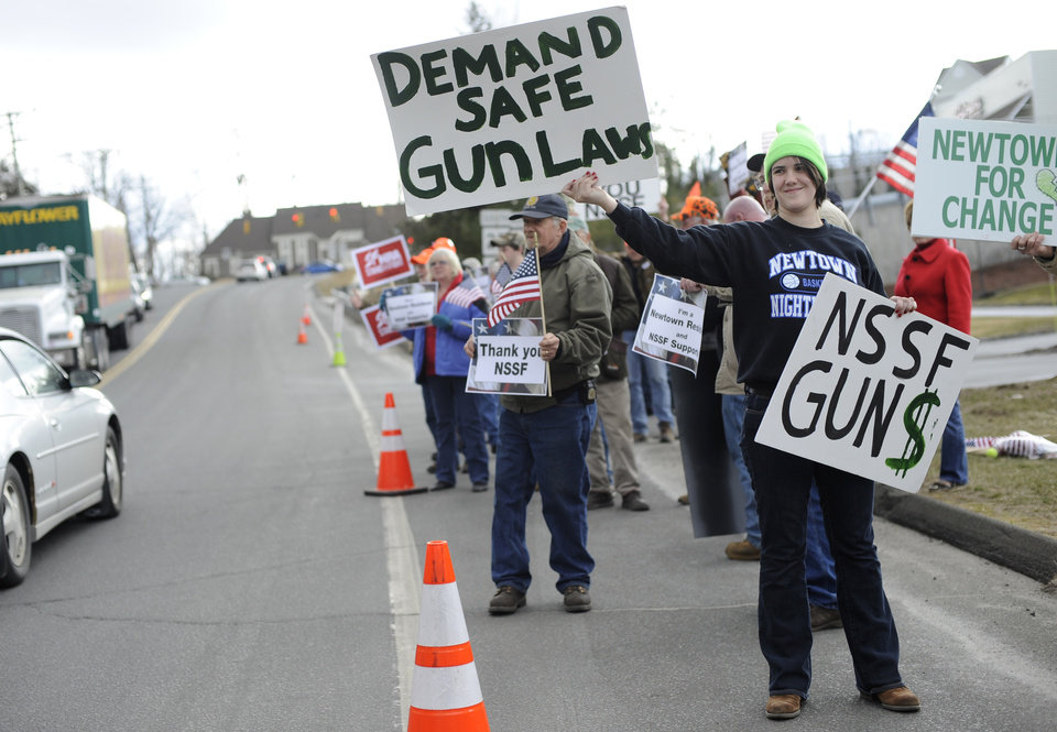Photo - Brady Eggleston of Newtown, a supporter of gun control stands in front of supporters for gun rights outside the National Shooting Sports Foundation headquarters  in Newtown, Conn., Thursday, March 28, 2013.  Search warrants released Thursday, March 28, 2013, revealed that an arsenal of weapons including guns, more than a thousand rounds of ammunition, a bayonet and several swords was seized at Adam Lanza's home.  Lanza killed his mother, Nancy Lanza in their home before he forced his way into Sandy Hook Elementary School in Newtown, Conn, killing 26 people.(AP Photo/Jessica Hill)