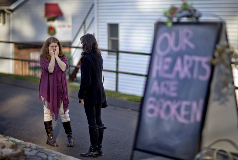 Photo - Shop owners Tamara Doherty, left, and Jackie Gaudet, right, meet outside their stores for the first time since being neighbors, just down the road from Sandy Hook Elementary School, Saturday, Dec. 15, 2012, in Newtown, Conn. The massacre of 26 children and adults at Sandy Hook Elementary school elicited horror and soul-searching around the world even as it raised more basic questions about why the gunman, 20-year-old Adam Lanza, would have been driven to such a crime and how he chose his victims. (AP Photo/David Goldman)