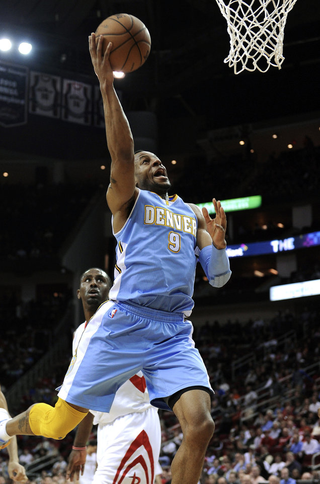 Photo - Denver Nuggets' Andre Iguodala (9) goes up for 2 points as Houston Rockets' Patrick Patterson, left, watches in the first half of an NBA basketball game Wednesday, Jan. 23, 2013, in Houston. (AP Photo/Pat Sullivan)