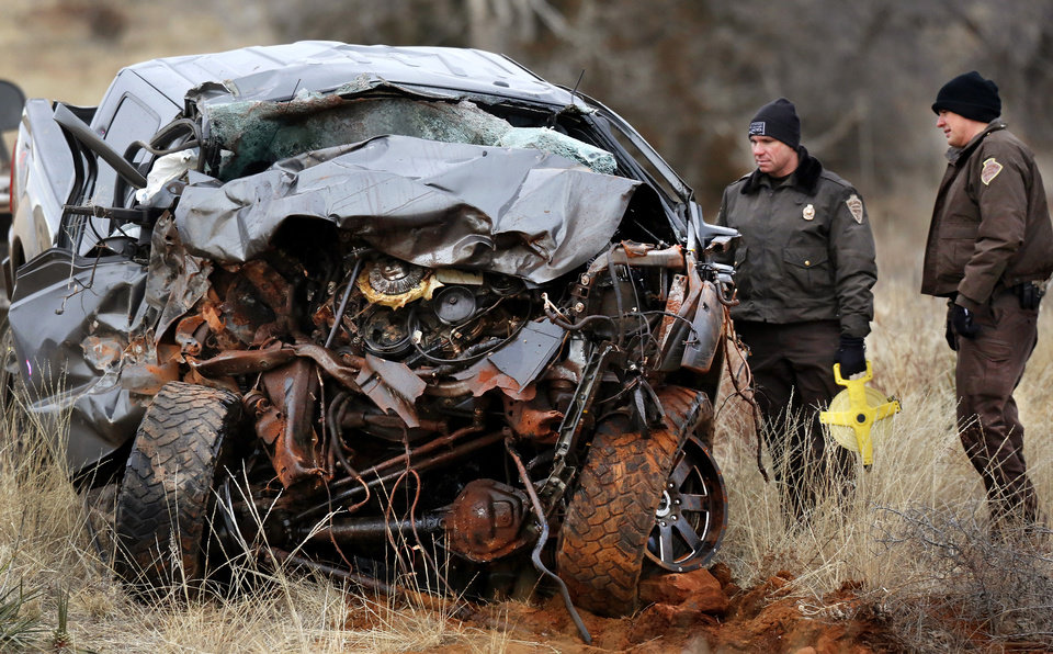 Photo - OHP investigators look at the wreckage of a 2011 Ford pickup truck driven by suspect Quentin Lee Johnson, 27, after it was pulled from a ravine where it landed after the driver ran off a two-- lane blacktop road east of Dill City.  Two officers died in a separate crash as they pursued this vehicle near Dill City. A Burns Flat police officer and an undersheriff for the Washita County Sheriff's Department died in a car crash on Thursday, Jan. 23, 2014, at a rural intersection about one mile south of Dill City.  According to OHP spokesman, the lawmen became involved in a high-speed pursuit  when a Washita County man fled as the undersheriff approached him to serve a felony warrant Thursday morning.  That same suspect died about the same time in another crash about three miles east of the location where the law officers collided. Dill City is located 75 miles west of Oklahoma City. Photo by Jim Beckel, The Oklahoman