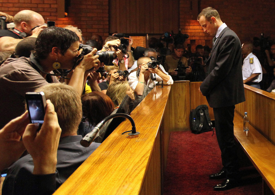 Photo - Olympic athlete Oscar Pistorius stands in the dock during his bail hearing at the magistrates court in Pretoria, South Africa, Friday, Feb. 22, 2013. The fourth and likely final day of Oscar Pistorius' bail hearing opened on Friday, with the magistrate then to rule if the double-amputee athlete can be freed before trial or if he has to remain in custody over the shooting death of his girlfriend. (AP Photo/Themba Hadebe)