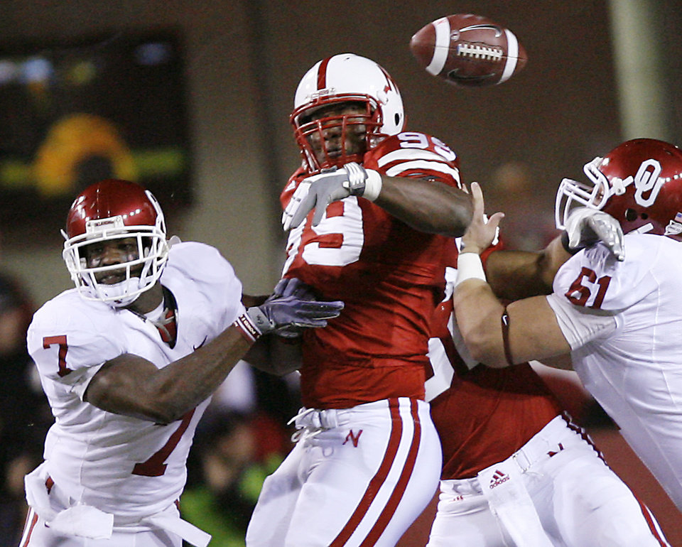 Photo - Nebraska's Barry Turner (99) breaks up a pass for Oklahoma's DeMarco Murray (7) during the first half of the college football game between the University of Oklahoma Sooners (OU) and the University of Nebraska Cornhuskers (NU) on Saturday, Nov. 7, 2009, in Lincoln, Neb.