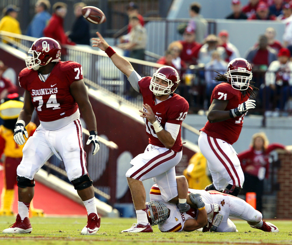 Photo - Oklahoma Sooner's Blake Bell (10) throws while in the arms of Iowa State Cyclone's Cory Morrissey (48) during the college football game between the University of Oklahoma Sooners (OU) and the Iowa State University Cyclones (ISU) at Gaylord Family-Oklahoma Memorial Stadium in Norman, Okla. on Saturday, Nov. 16, 2013. Photo by Steve Sisney, The Oklahoman