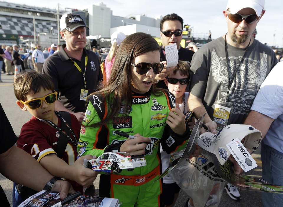 Danica Patrick signs autographs for fans after her qualifying run for Saturdays NASCAR Nationwide Series auto race, Friday, Feb. 22, 2013, at Daytona International Speedway in Daytona Beach, Fla. (AP Photo/Chris O'Meara)  ORG XMIT: DBR221