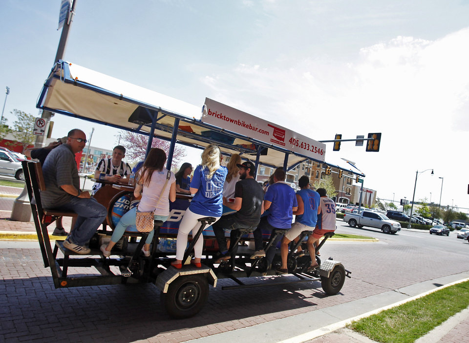 Photo -  Customers are on the Bricktown Bike Bar on Saturday around Bricktown. The vehicle is powered by 10 riders who pedal and drink. Photos by K.T. King, The Oklahoman    -  OPUBCO