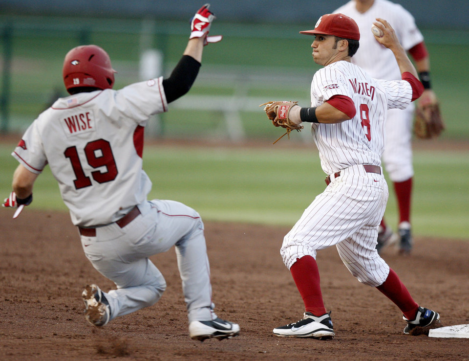 Photo - Oklahoma's Jack Mayfield throws past Arkansas' Jake Wise to first for a double play in the fifth inning of their baseball game at L. Dale Mitchell Park in Norman, Okla., Tuesday, April 10, 2012. Photo by Bryan Terry, The Oklahoman