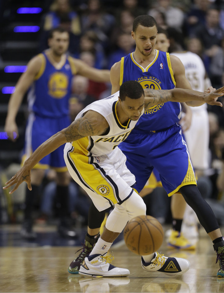 Photo - Indiana Pacers' George Hill, left, is defended by Golden State Warriors' Stephen Curry (30) during the first half of an NBA basketball game Tuesday, March 4, 2014, in Indianapolis. (AP Photo/Darron Cummings)