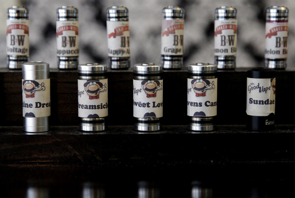 Photo -  An electronic cigarette e-liquid display is shown at Vape store in Chicago,.  AP Photo   Nam Y. Huh -  AP