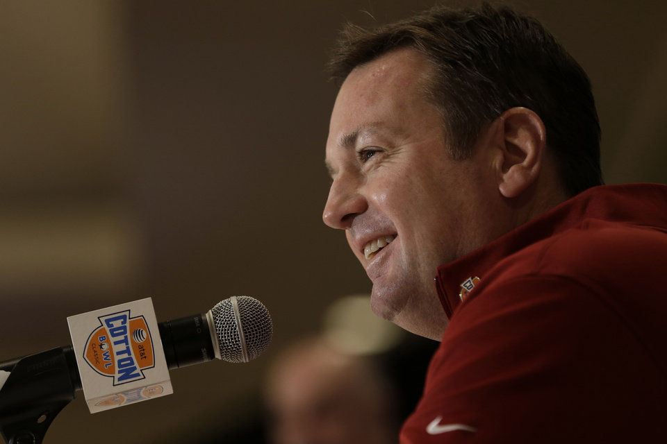 Photo - Oklahoma head coach Bob Stoops smiles as he answers a question during a news conference leading up to the Cotton Bowl NCAA college football game Wednesday, Jan. 2, 2013, in Irving, Texas. Before Texas A&M head coach Kevin Sumlin became a succesful head coach, he was on Stoops' staff at Oklahoma. Before that, they were both assistant coaches recruiting the same area. Now Sumlin takes his Texas A&M team against Stoops' Sooners in a Jan. 4th Cotton Bowl matchup of former Big 12 rivals that are both 10-2. (AP Photo/LM Otero) ORG XMIT: TXMO107