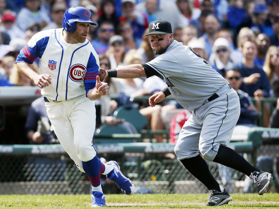 Photo - Chicago Cubs' Nate Schierholtz, left, is tagged out by Miami Marlins third baseman Casey McGehee on a run down during the sixth inning of a baseball game on Sunday, June 8, 2014, in Chicago. (AP Photo/Andrew A. Nelles)