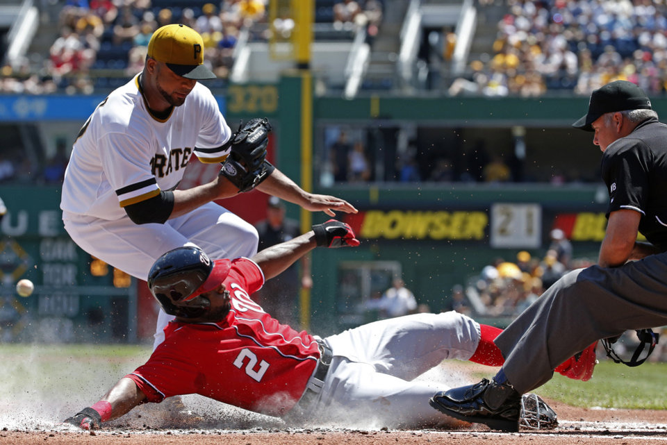 Photo - Washington Nationals' Denard Span (2) scores from third on a wild pitch by Pittsburgh Pirates starting pitcher Francisco Liriano, left, as umpire Tim Timmons watches the play during the first inning of a baseball game in Pittsburgh Sunday, May 25, 2014. (AP Photo/Gene J. Puskar)