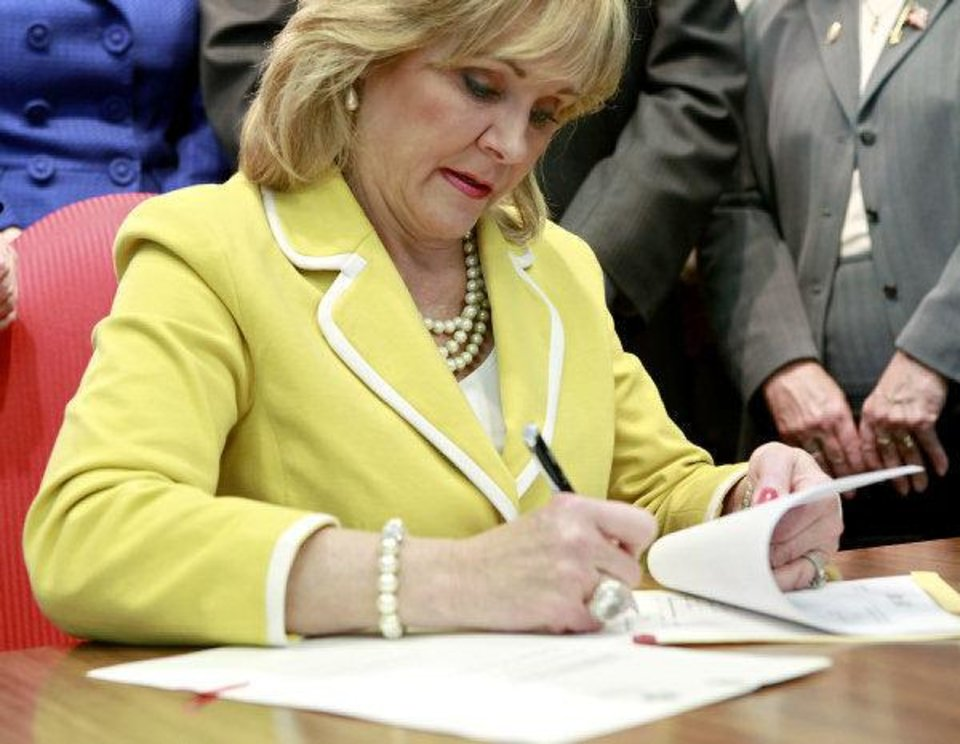 Photo - Oklahoma Governor Mary Fallin signs Senate Bill 346 during a press conference at the Oklahoma State Capitol in Oklahoma City on May 4, 2011. Fallin signed two bills on Wednesday, Senate Bill 346 ends social promotion for students after the third grade and  House Bill 1456 creates an A-F system for public schools. Photo by John Clanton, The Oklahoman ORG XMIT: KOD