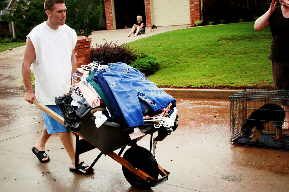 Photo - A man salvages clothes from his home in the Palo Verde subdivision in Edmond, Okla. Monday, June 14, 2010.  Photo by Jordon Shinn, The Oklahoman