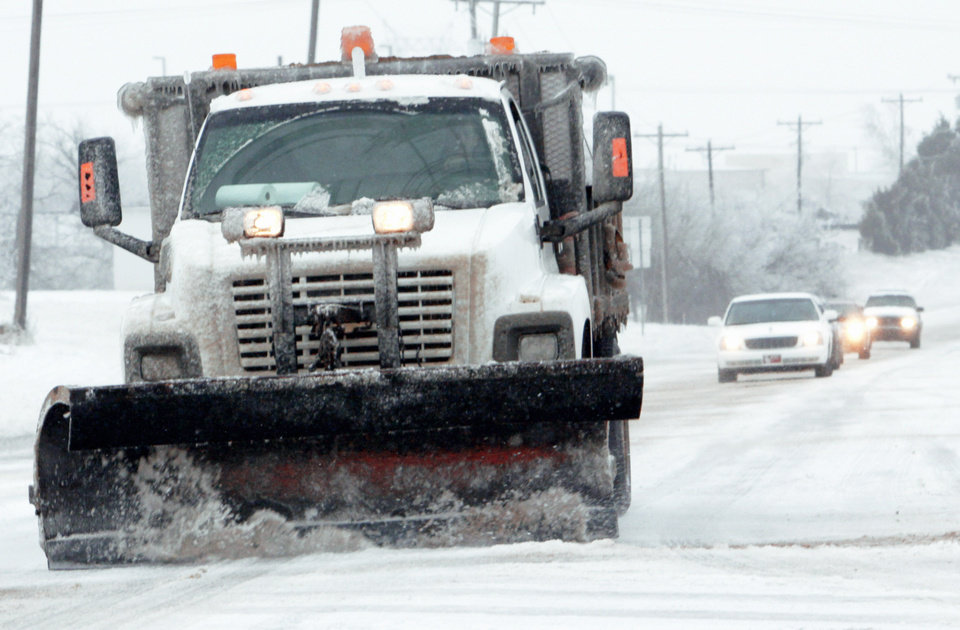 A snowplow travels south on Flood Avenue near Tecumseh Road on Friday morning.  PHOTO BY STEVE SISNEY, THE OKLAHOMAN