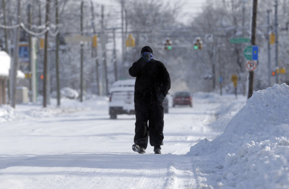 Photo - A pedestrian makes their way along a snow packed street in Indianapolis Monday, Jan. 6, 2014, as temperatures hovered around 10 below zero. More than 12 inches of snow fell on Sunday. (AP Photo/Michael Conroy)