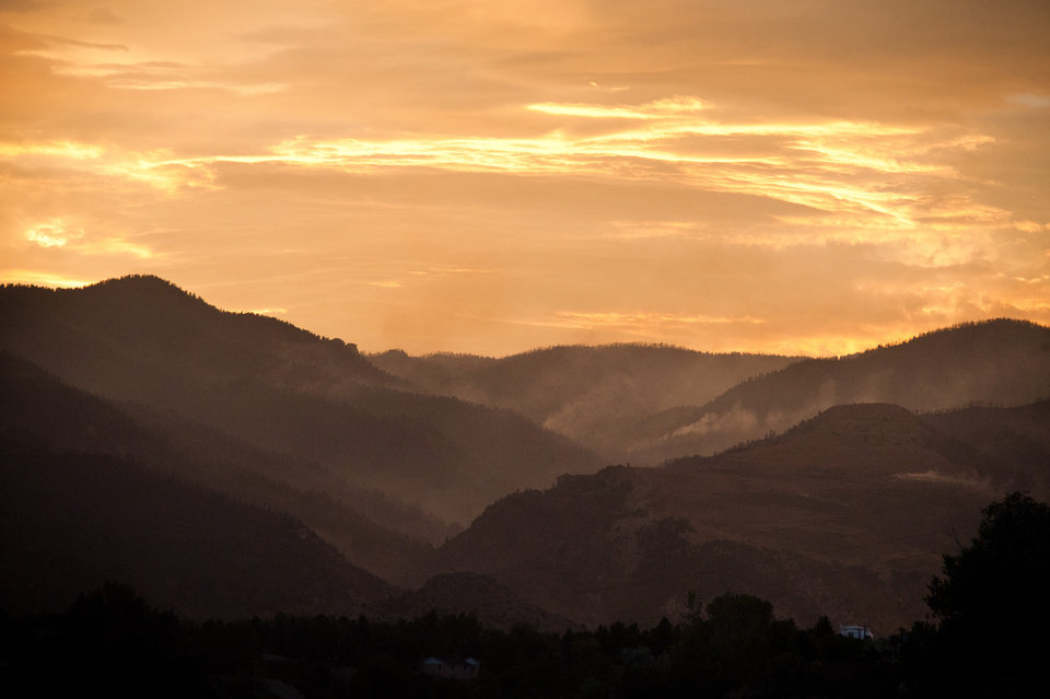 Photo -   Light smoke is visible in Queen's Canyon as the sun sets on the fifth day of the Waldo Canyon Fire burning west of Colorado Springs, Colo. Wednesday, June 27, 2012. On Tuesday the fire jumped Queen's Canyon to begin it's run into Colorado Springs where it destroyed several homes. (AP Photo/The Colorado Springs Gazette,Mark Reis )