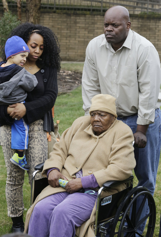 Photo - Bernice Youngblood, 85, center, a resident of the East Neck Nursing and Rehabilitation Center, listens during a news conference on the lawn of the nursing home with her granddaughter, Saniya Delgado and great-grandson Antonio, 2, left, and son, Darrell, right, Tuesday, April 8, 2014, in West Babylon, N.Y. The nursing home a hired male exotic dancer to perform for its patients, according to a lawsuit filed by Youngblood in State Supreme Court in Suffolk County. (AP Photo/Mark Lennihan)