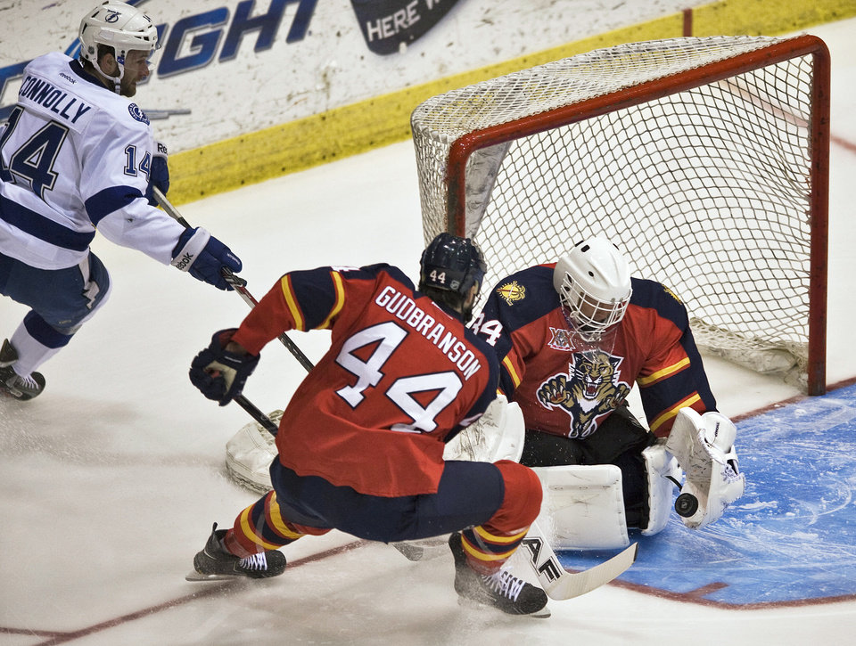 Photo - Florida Panthers defender Erik Gudbranson (44) watches as goalie Tim Thomas, right, stops a shot from Tampa Bay Lightning' Brett Connolly (14) during the first period of an NHL preseason hockey game Thursday, Sept. 26, 2013, in Estero, Fla. (AP Photo/Steve Nesius)